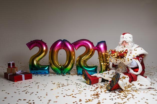 Oude vader vorst met kleurrijke ballonnen met cijfers 2021 heeft een cadeautje