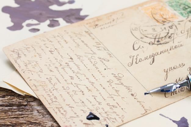 Oude veren pen op handgeschreven brieven achtergrond
