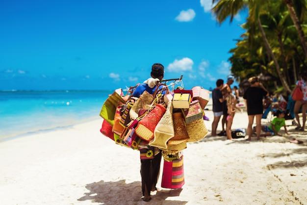 Oude verkoper die onderaan helder strand loopt dat met de hand gemaakte vrouwentoebehoren verkoopt