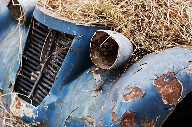 Oude verlaten auto met hooi op motor
