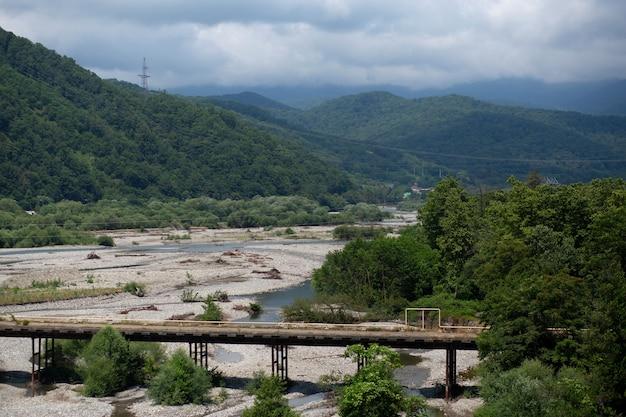 Oude verlaten brug en bergrivier in de vallei, groene bomen, mooi landschap