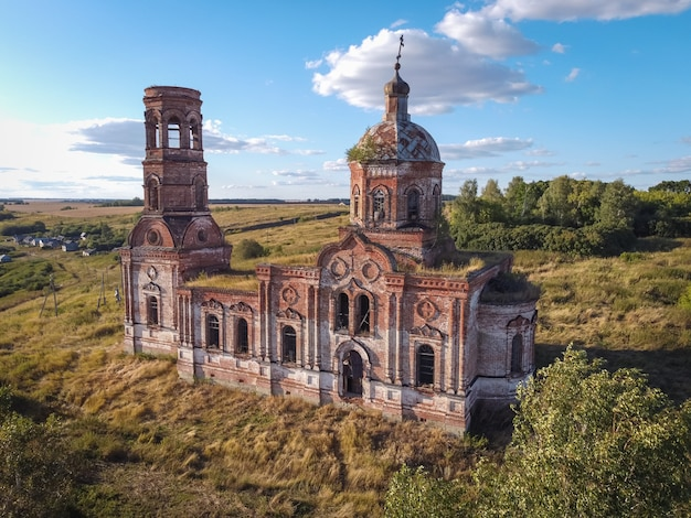 Oude verlaten en verwoeste kerk, vervallen tempel van rode baksteen, verlaten tempel van rode baksteen