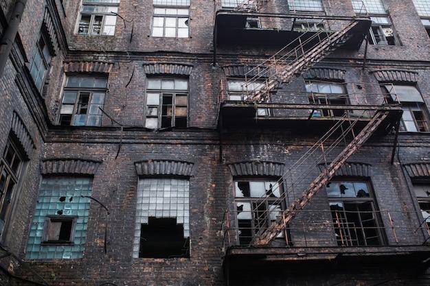 Oude verlaten fabriek. gotische industriële achtergrond. enge plek. post-apocalyptisch landschap. halloween-feestplaats. verlaten gebouw. industriële grunge achtergrond. nucleaire oorlog. griezelige fabriek