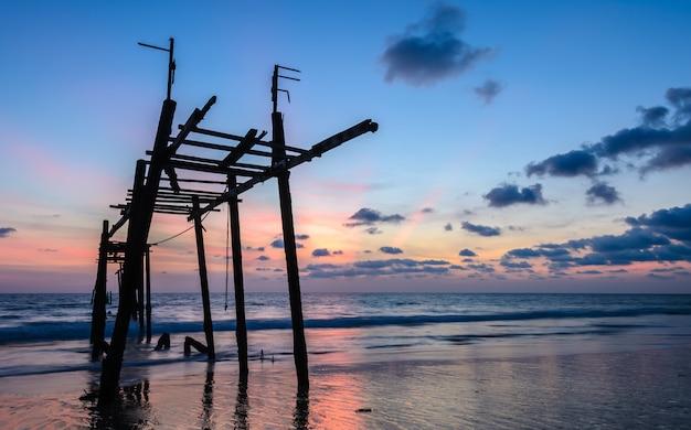 Oude verlaten houten brug met de hemel van de zeegezichtzonsondergang