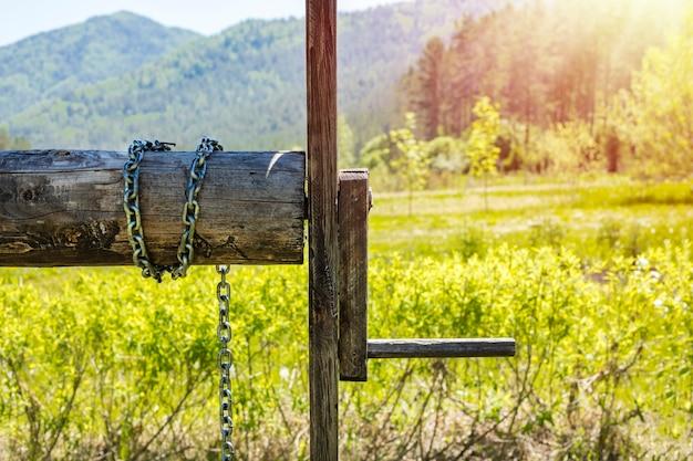 Oude verlaten houten put met mooie structuur op platteland. tegen de achtergrond van prachtige natuur