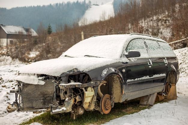Oude verlaten verlaten roestige gebroken die afvalauto met sneeuw wordt behandeld