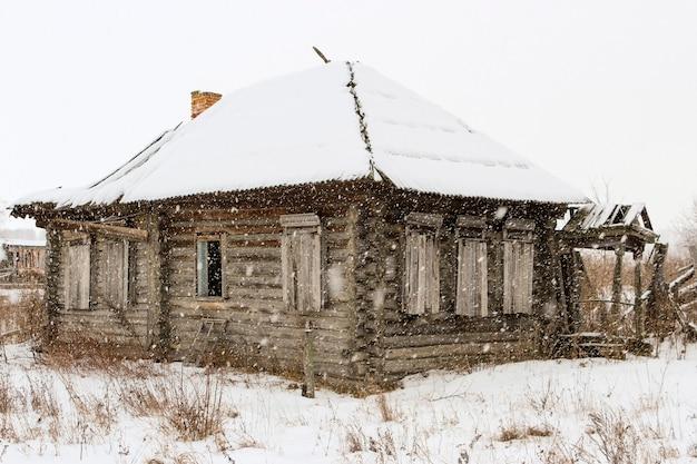 Oude verlaten vervallen houten huis bedekt met sneeuw