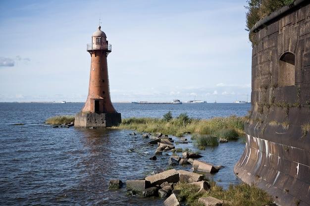 Oude verlaten vuurtoren in de buurt van de kust op een zonnige dag
