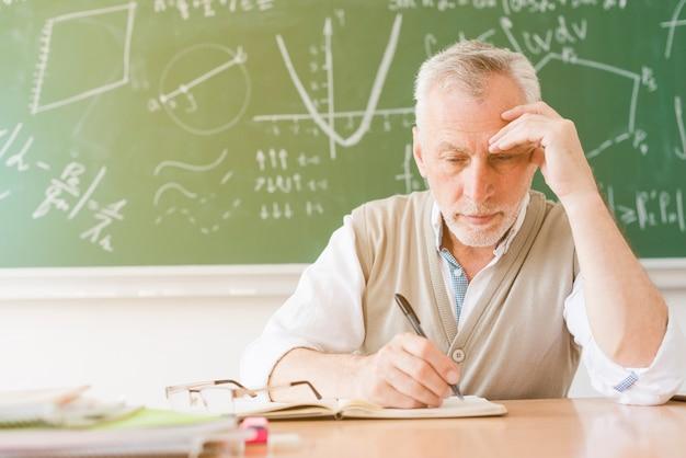 Oude vermoeide leraar die in notitieboekje in klaslokaal schrijft