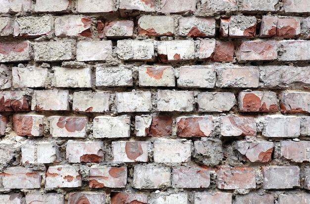 Oude vernietigde rode bakstenen muur als achtergrond vooraanzicht horisontal close-up