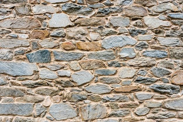 Oude, verschillende de muur van de kleurensteen textuur dichte omhooggaand als achtergrond