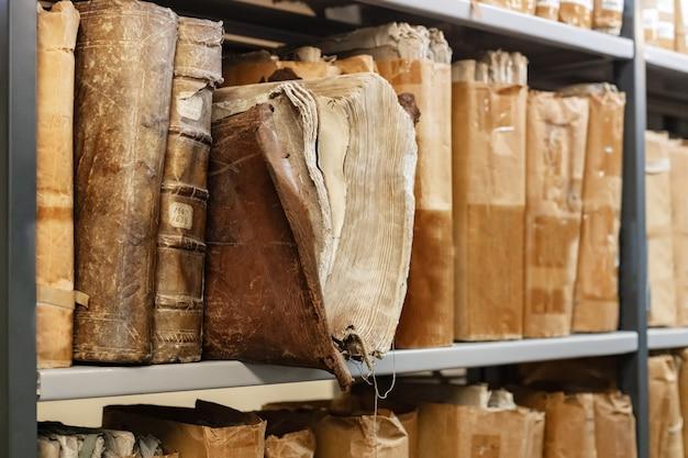 Oude versleten 17e-eeuwse boeken op een plank in de bibliotheekarchieven