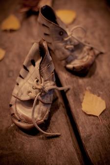 Oude versleten babyschoenen op de stoeptegel. het concept van armoede