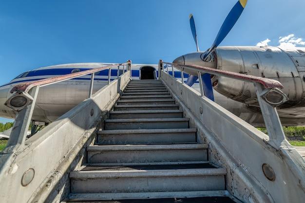 Oude, versleten passagiersgang. gangway vastgemaakt aan het vliegtuig.