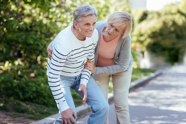 Oude verwarde paniekerige man die lijdt aan pijn in de knie en frustratie uitdrukt terwijl een oude vrouw hem buitenshuis helpt