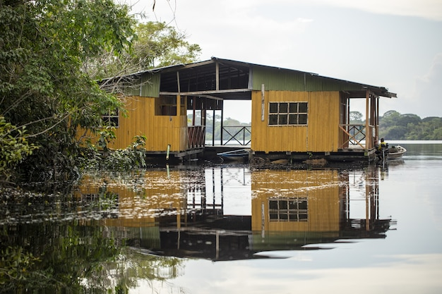 Oude verweerde gele houten hut aan het meer omgeven door prachtig groen