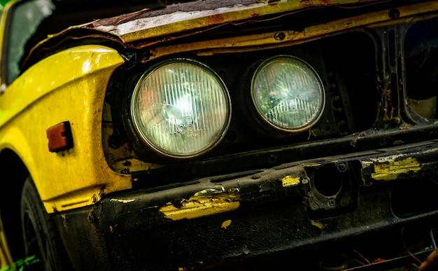 Oude verwoeste auto in vintage stijl. verlaten roestige gele auto in het bos
