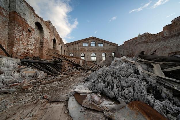 Oude verwoeste bakstenen gebouw, muren. zonder dak, onder een open blauwe lucht. stapels vuilnis erin.
