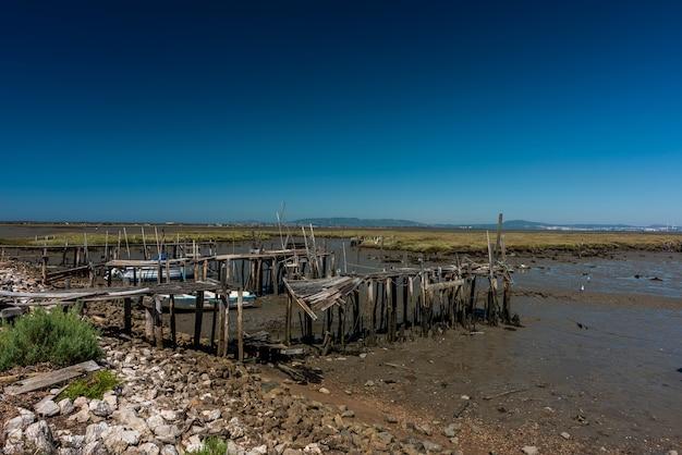 Oude verwoeste houten dek aan de kust onder het zonlicht in cais palafitico da carrasqueira, portugal
