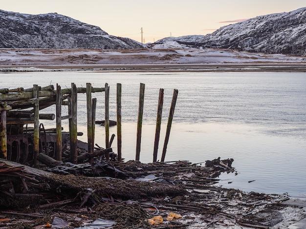 Oude verwoeste houten pier in de baai van de barentsz-zee. teriberka. vervuiling van de kustlijn. rusland.