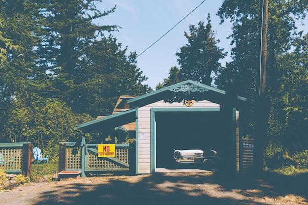 Oude vintage auto geparkeerd in een kleine garage naast een bord op een hek