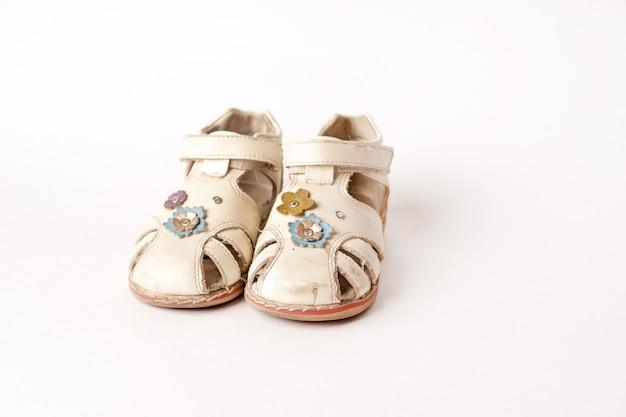 Oude vintage babysandalen op wit