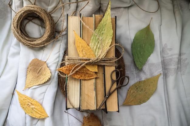 Oude vintage boeken en herfstbladeren op een lichte achtergrond