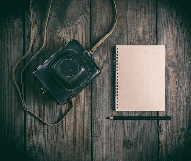 Oude vintage camera in een lederen tas en een notitieblok met een houten zwart potlood
