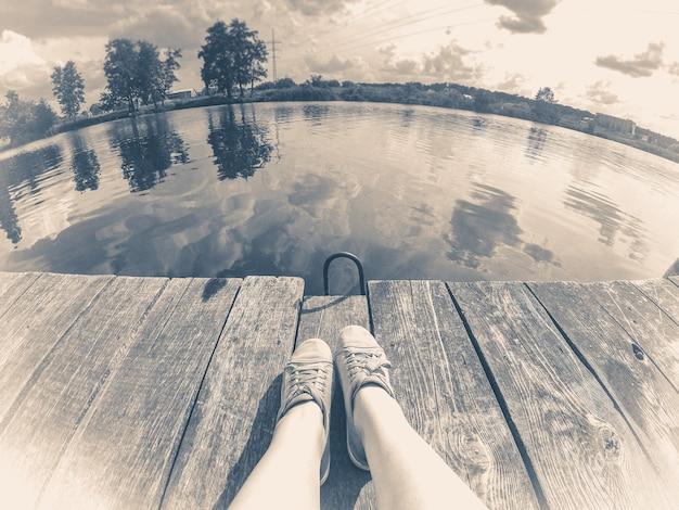 Oude vintage foto. meisje in spijkerbroek zit op de oude kade in het close-up van het meer.