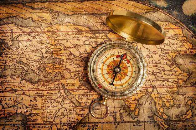 Oude vintage gouden kompas op oude kaart