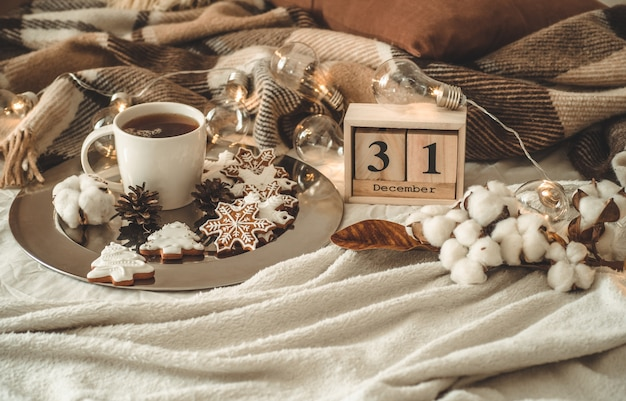 Oude vintage houten kalender ingesteld op 31 december met kopje thee.