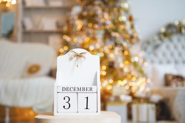 Oude vintage kalender van houten kubussen met de datum van 31 december op de achtergrond van een kerstboom met brandende wazige lichten. geselecteerde focus op de voorgrond.
