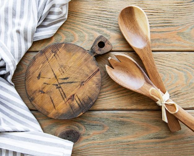 Oude vintage keukengerei. houten lepels, snijplank, servet. over oude houten tafel. bovenaanzicht
