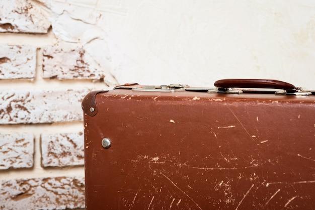 Oude vintage koffer in de betonnen lichte kamer.