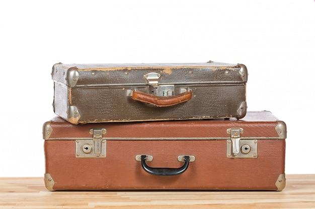 Oude vintage koffers op lichte houten tafel geïsoleerd
