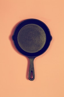 Oude vintage pan op roze mode achtergrond. toning. bovenaanzicht. kookconcept.