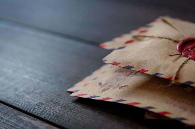 Oude vintage retro enveloppen met een wasstempel op oude donkerbruine houten tafel