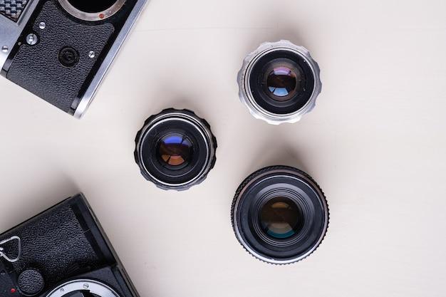 Oude vintage retro foto film afstandsmeter camera en spiegelreflexcamera zonder lens bevestigd in de buurt met drie lenzen, bovenaanzicht op witte muur