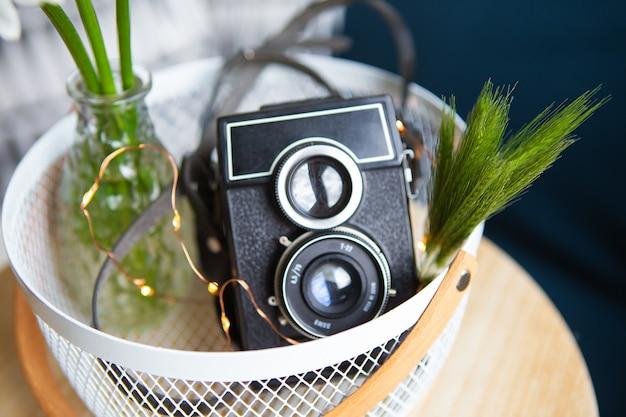 Oude vintage rustieke camera met een boeket van madeliefjebloemen op een houten bord.