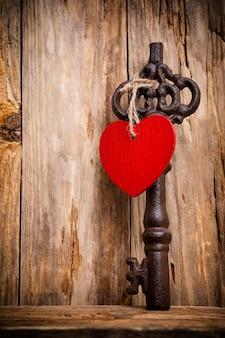 Oude vintage sleutel met hart op houten achtergrond.