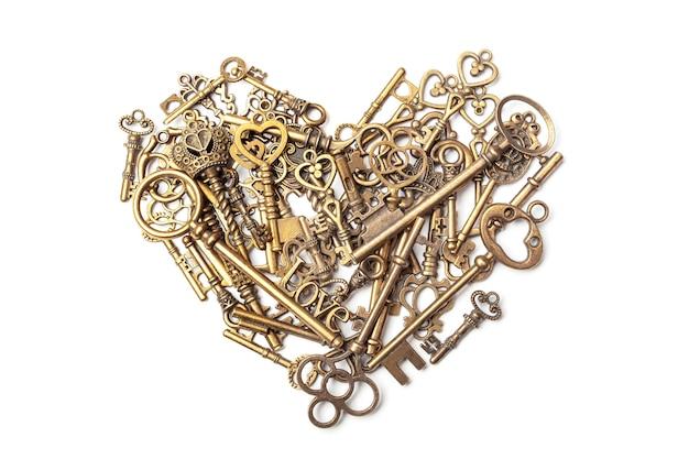 Oude, vintage sleutels in de vorm van een hart op wit wordt geïsoleerd