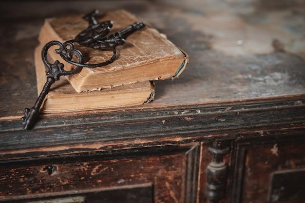 Oude vintage sleutels op een oud gehavend boek in antiek houten meubilair. het concept van mysterie en ontdekking