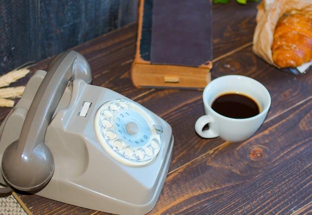 Oude vintage telefoon, koffie, boek, op een houten achtergrond,