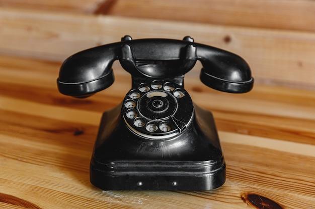 Oude vintage zwarte telefoon op houten tafel.