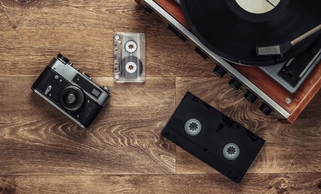 Oude vinyl platenspeler, videocassettes, audiocassette, ouderwetse filmcamera op de vloer. retro media jaren 80. bovenaanzicht