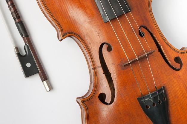 Oude viool met een boog op een witte achtergrond