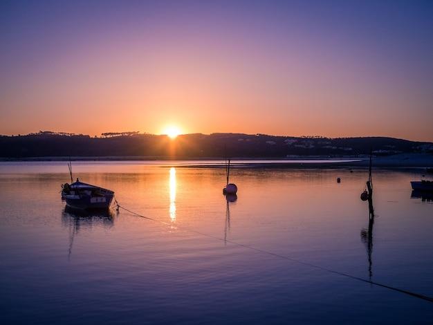Oude vissersboot bij de rivier met het adembenemende uitzicht op de zonsondergang