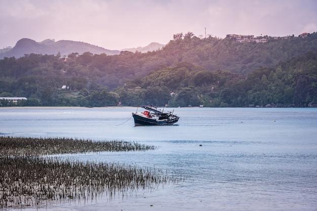 Oude vissersboot dichtbij een kust ot tropisch eiland