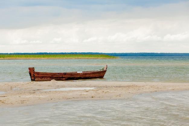 Oude vissersboot in zonsopgangtijd op het strand