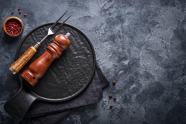 Oude vleesvork, lege houten standaard, zwarte peper en zwarte peper en kruidenmolen op een oude grijze betonnen ondergrond. voedsel koken achtergrond en mock up.